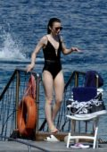 Lily Collins in a Black Swimsuit relaxes on the Beach in Ischia, Italy