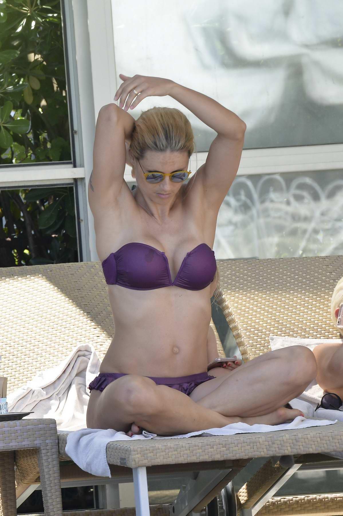 Michelle Hunziker relaxing by the Pool in a Purple Bikini