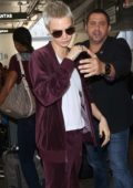 Cara Delevingne in a Suede Maroon Track Suit arrives at LAX Airport in Los Angeles