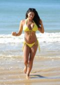 Casey Batchelor in a yellow bikini on beach in Portugal