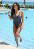 Casey Batchelor in a blue denim Swimsuit relaxing by the poolside in Portugal