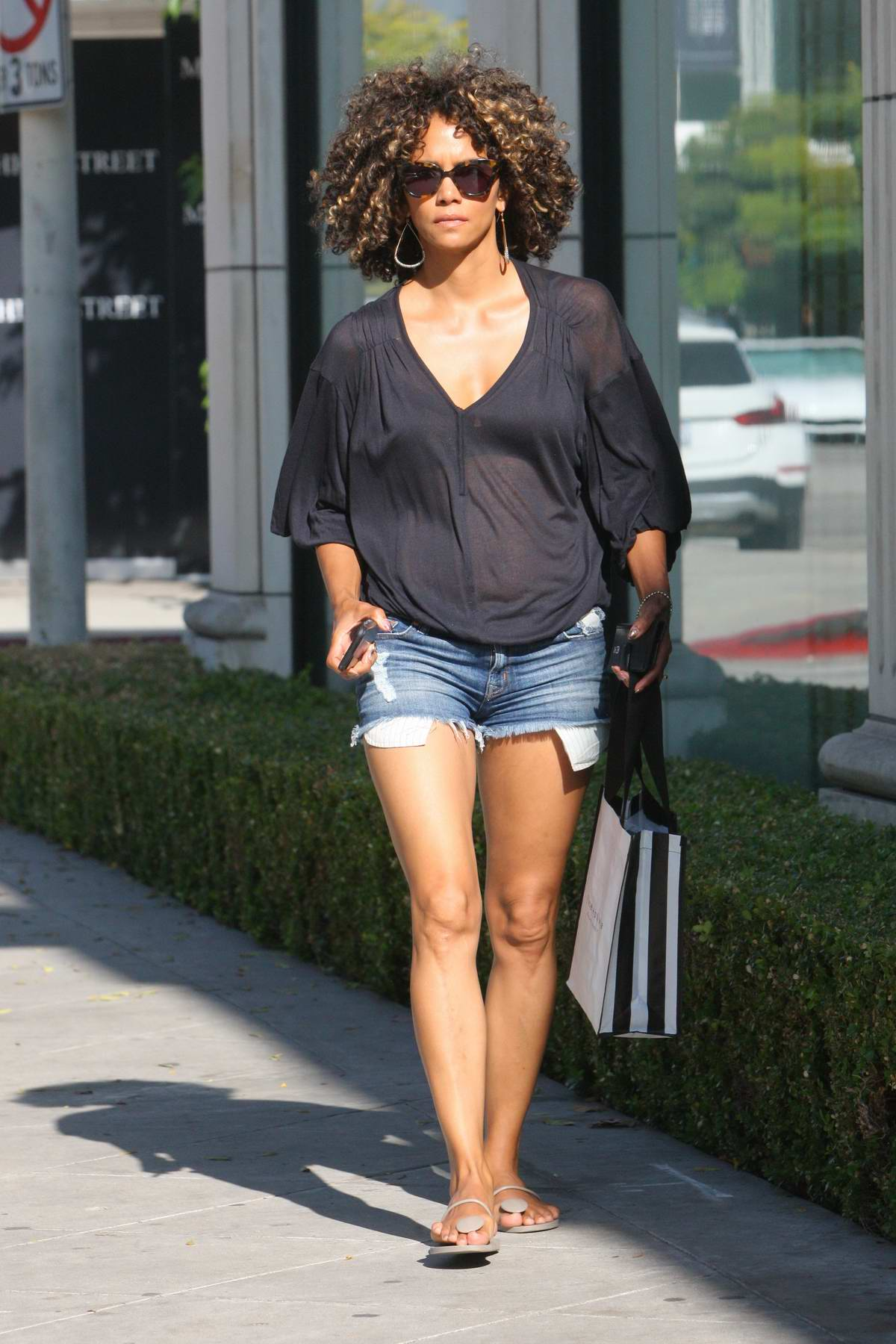 Halle Berry wearing see through Shirt and Demin Short while shopping on Melrose Avenue in West Hollywood