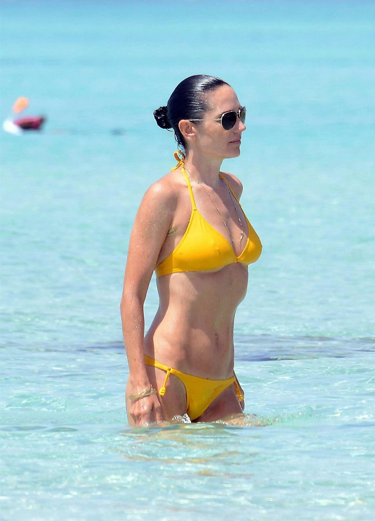 Jennifer Connelly in a yellow bikini enjoying the ocean while on holiday in Spain