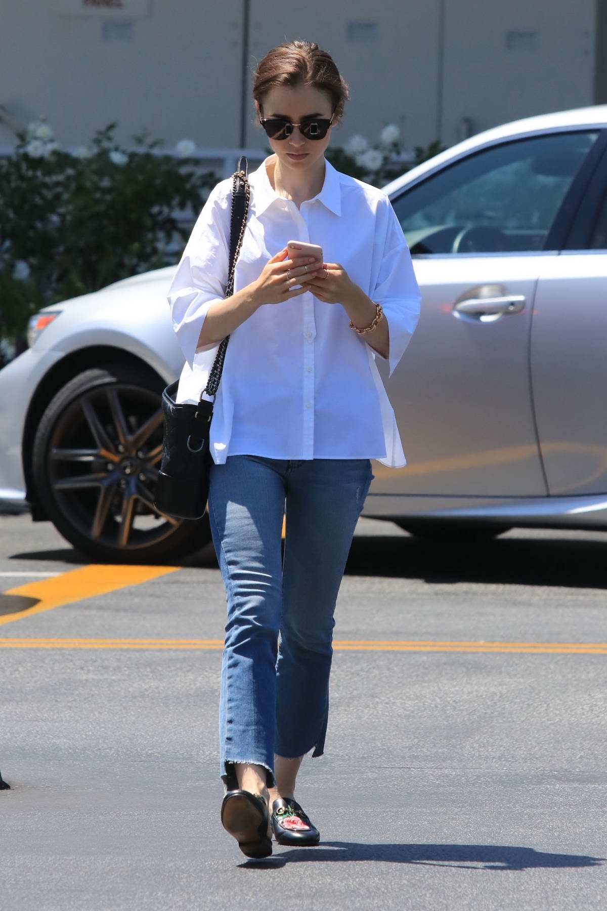Lily Collins running errands in casual white shirt and jeans in Los Angeles