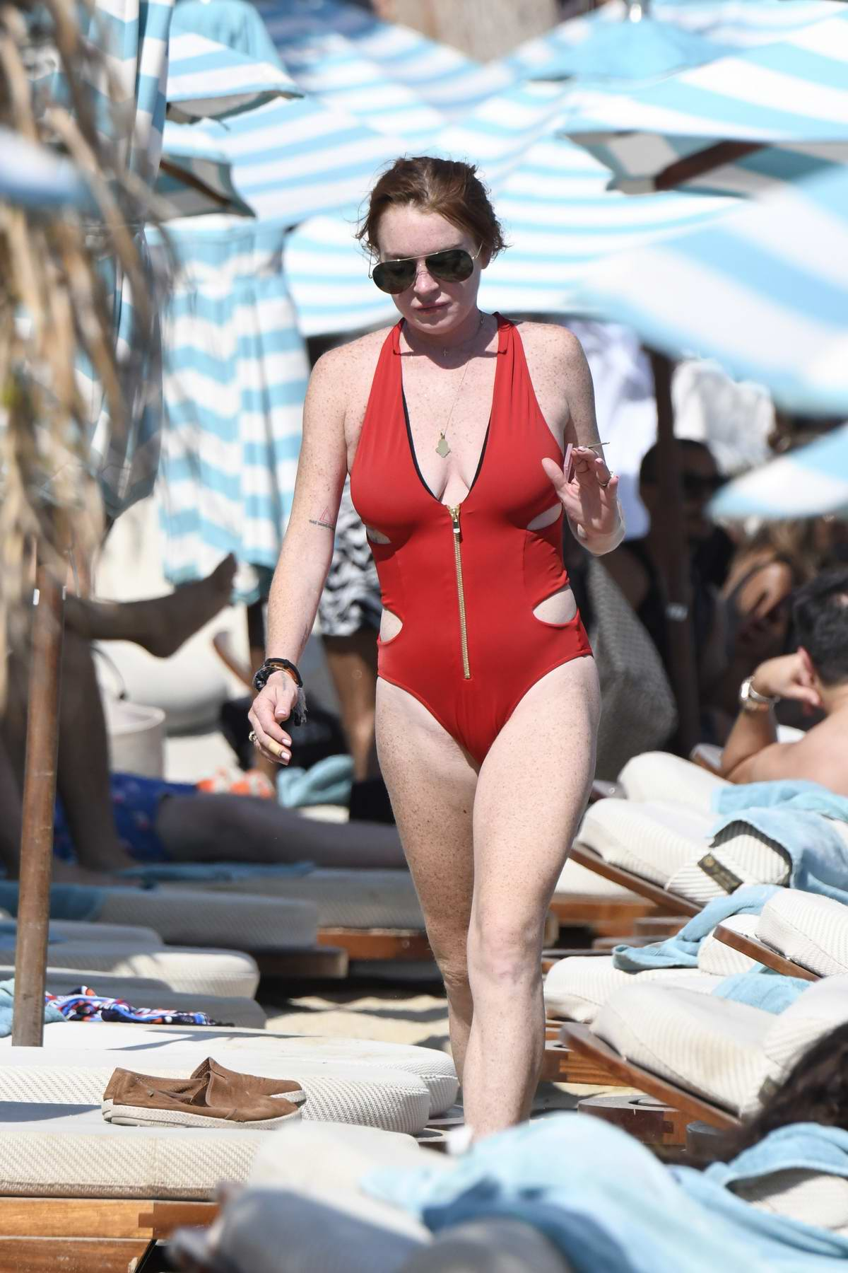 Lindsay Lohan in red swimsuit relaxing on the beach in Mykonos, Greece