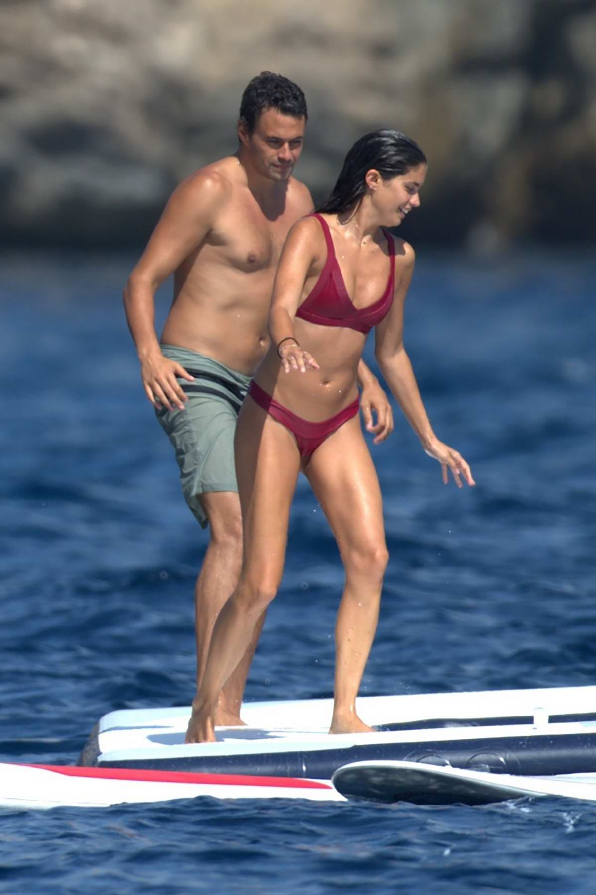 Sara Sampaio in a red bikini enjoys a dip with boyfriend Oliver Ripley on board of a Yacht in Ibiza, Spain