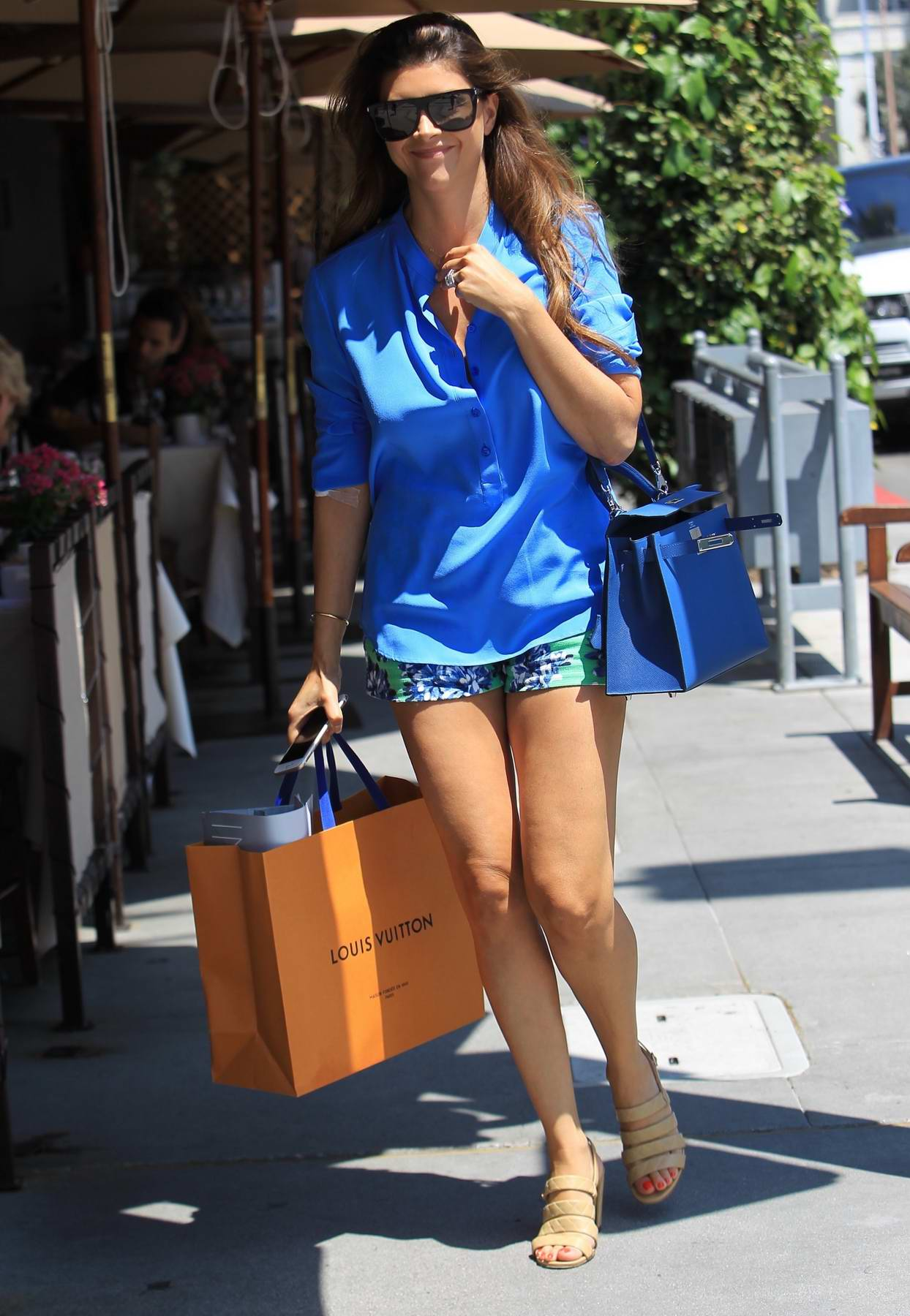 Shiva Safai in a bright blue shirt and shorts out shopping in Beverly Hills, Los Angeles