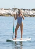 Tallia Storm in a checkered swimsuit rides a Paddle board in Marbella, Spain