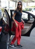 Alessandra Ambrosio in a black tee and red pants arrives for milan fashion week in Milan, Italy