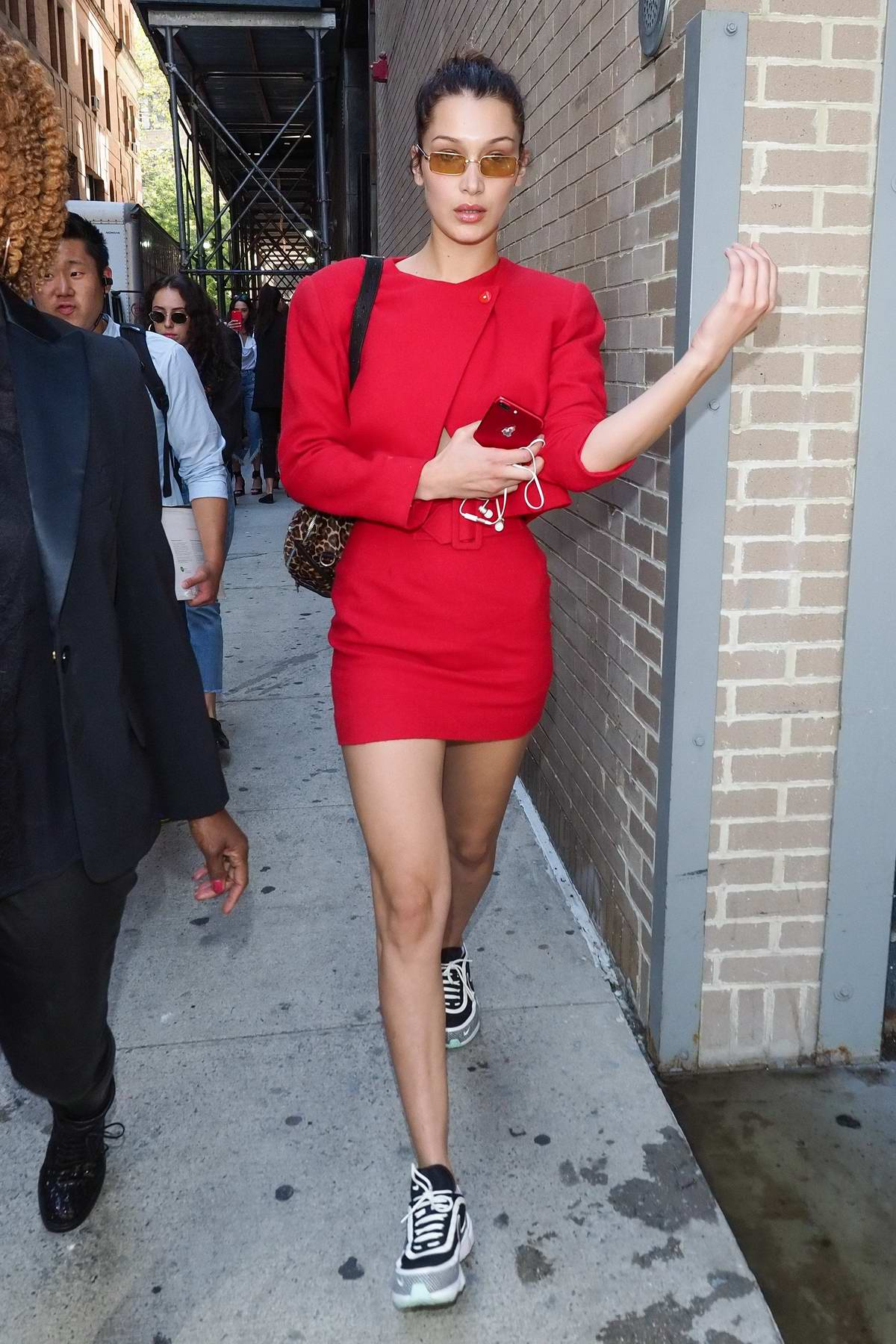 Bella Hadid in a short red dress leaves work during New York Fashion Week