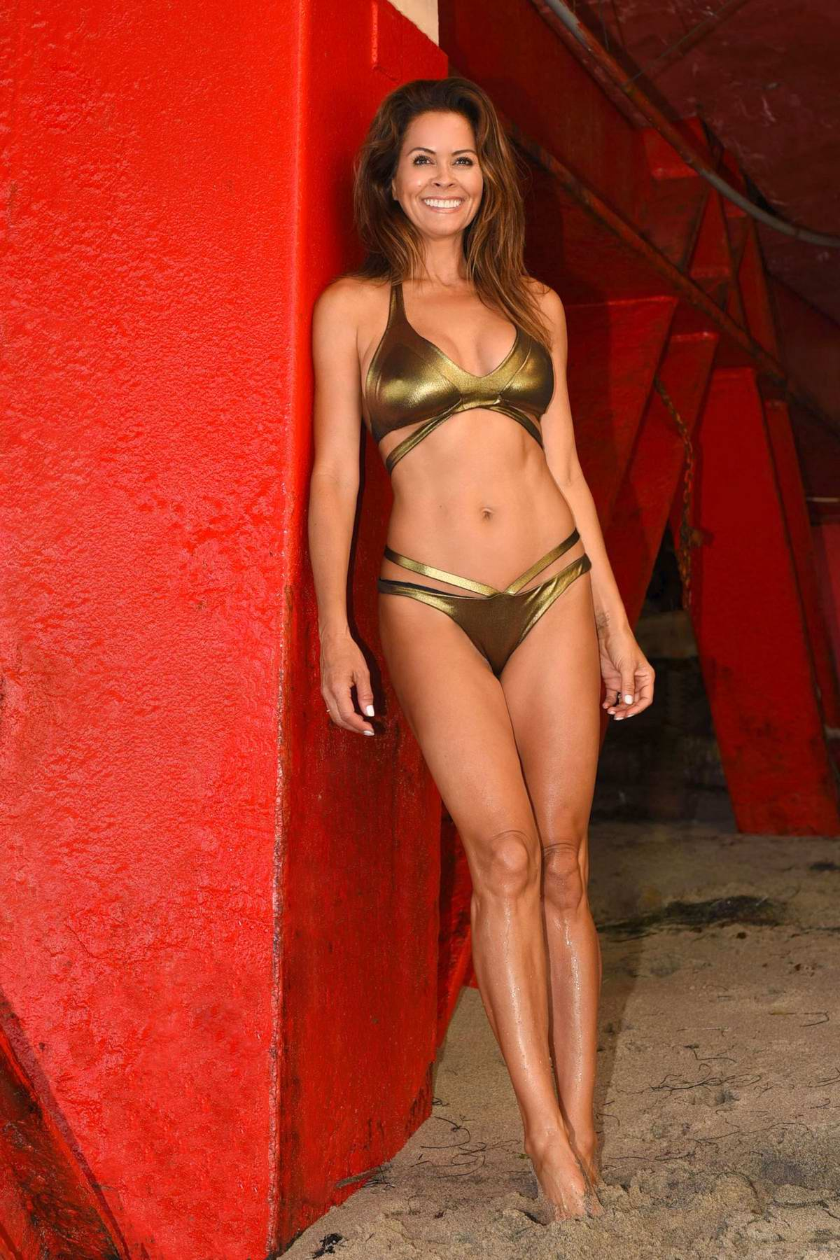 Brooke Burke in a golden bikini enjoying her summer break in Malibu, California