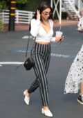 Chantel Jeffries in a plunging top and striped pants returns to her car after having lunch with friends at Fred Segal in West Hollywood, Los Angeles