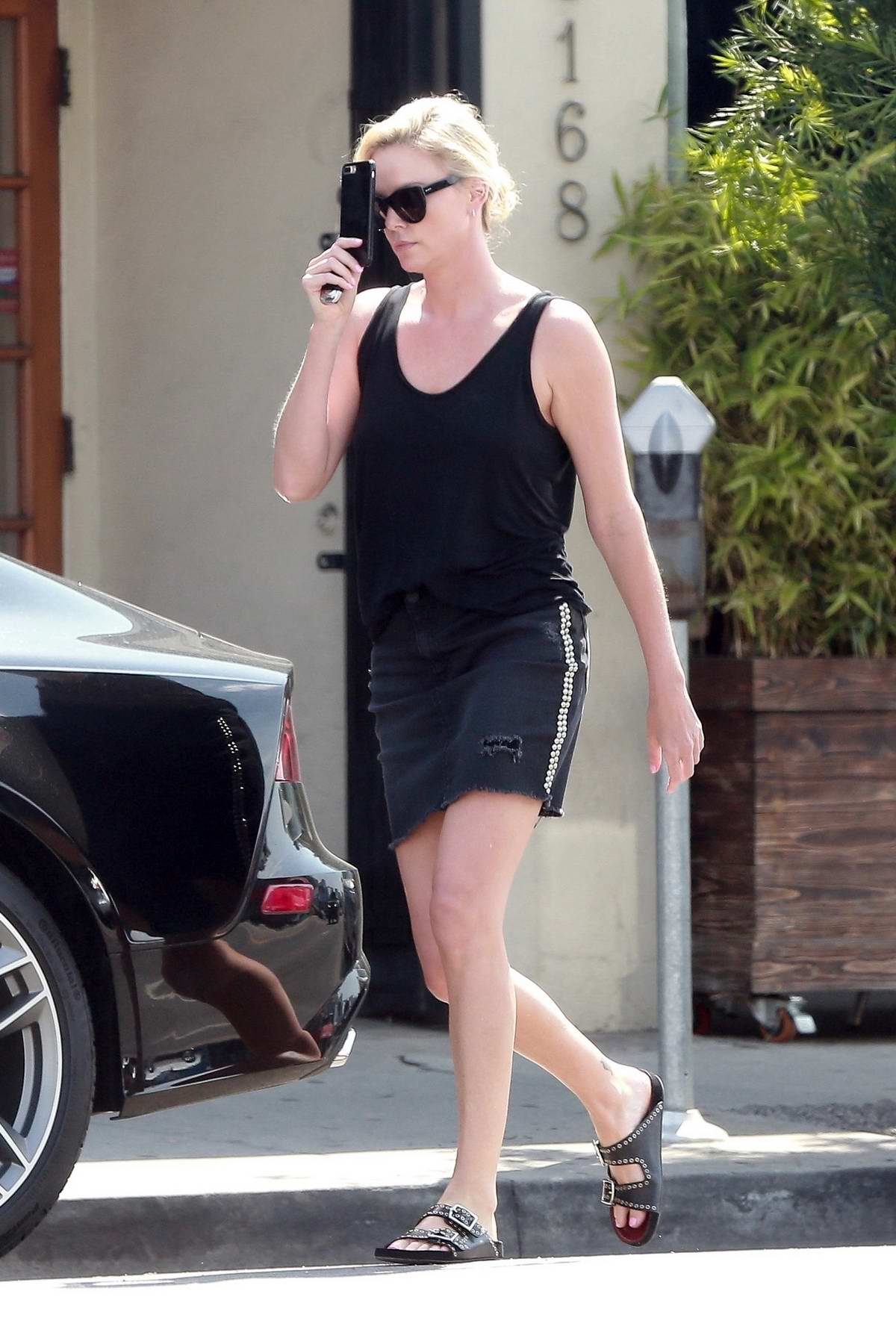 Charlize Theron dons a black crop top with matching denim skirt while shopping in West Hollywood, Los Angeles