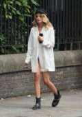 Chloe Lloyd wearing a white jacket while walking around in London