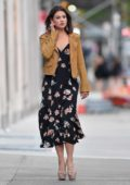 Danielle Campbell seen wearing a tan leather jacket over a black floral dress in New York City