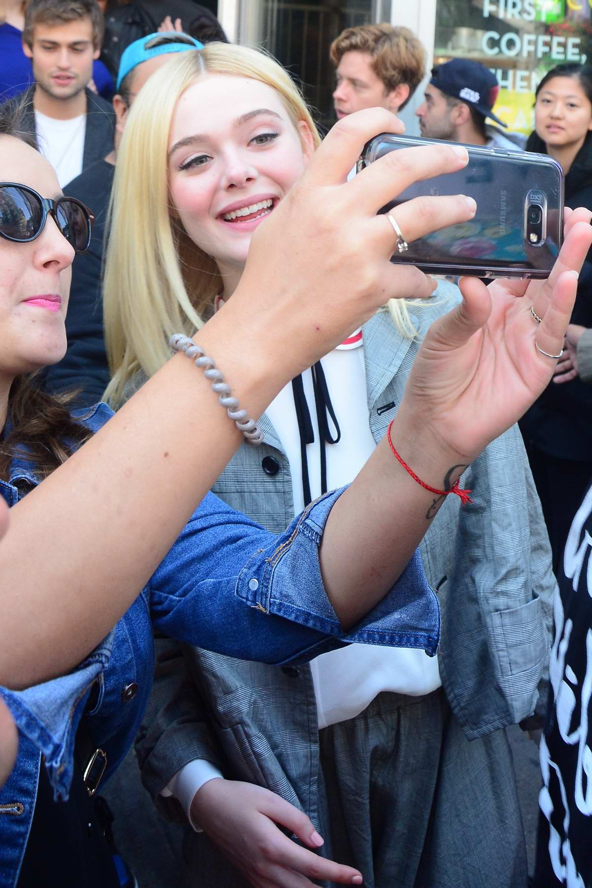Elle Fanning takes selfies with fans while leaving press conference during Toronto International Film Festival, Canada
