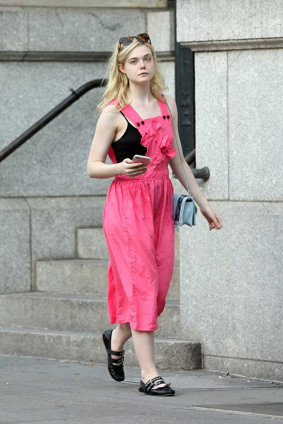 Elle Fanning wearing pink overall with black top returns home in Soho in New York City