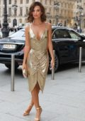 Emily Ratajkowski in a golden deep cut dress arriving at Harper's Bazaar 150th Anniversary during Paris Fashion Week, France