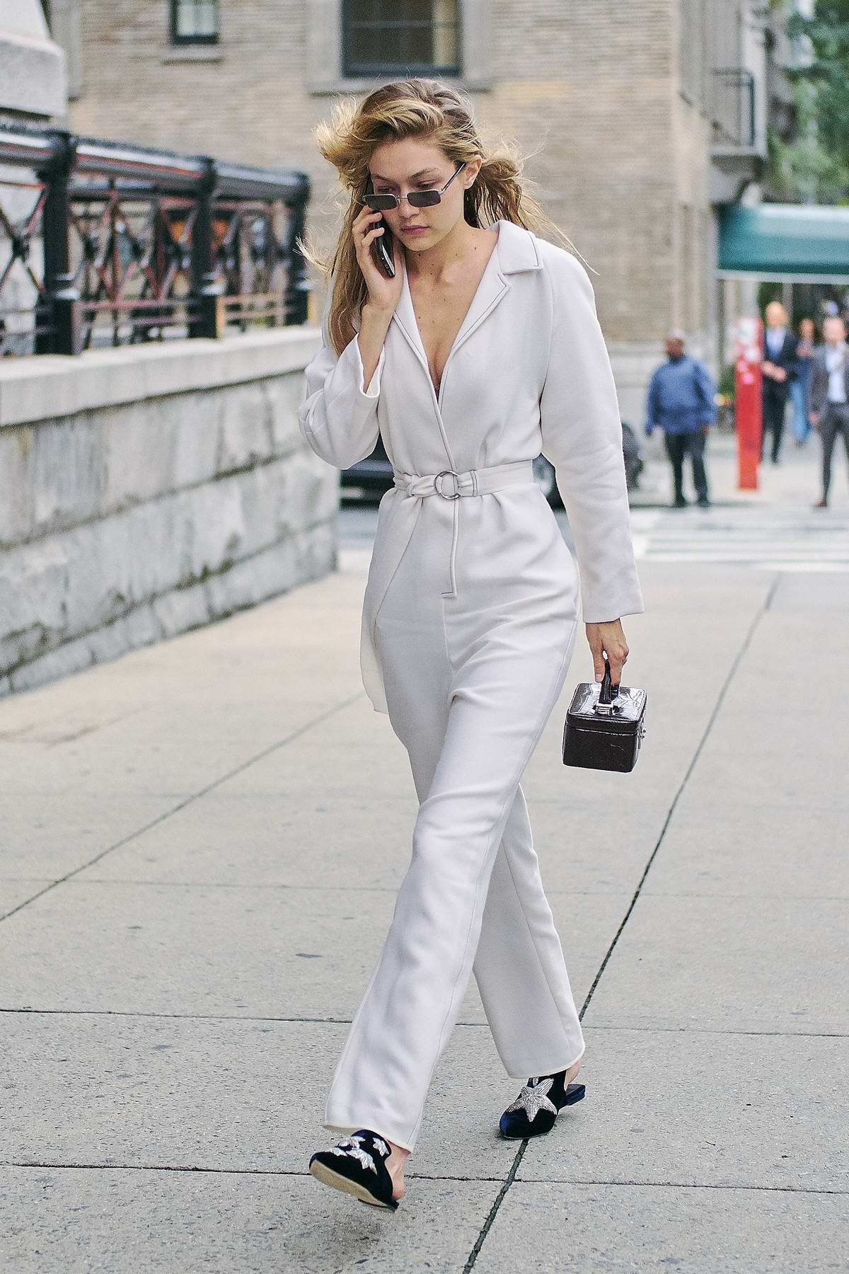 Gigi Hadid wearing all white while arriving at the Tom Ford fashion show in New York
