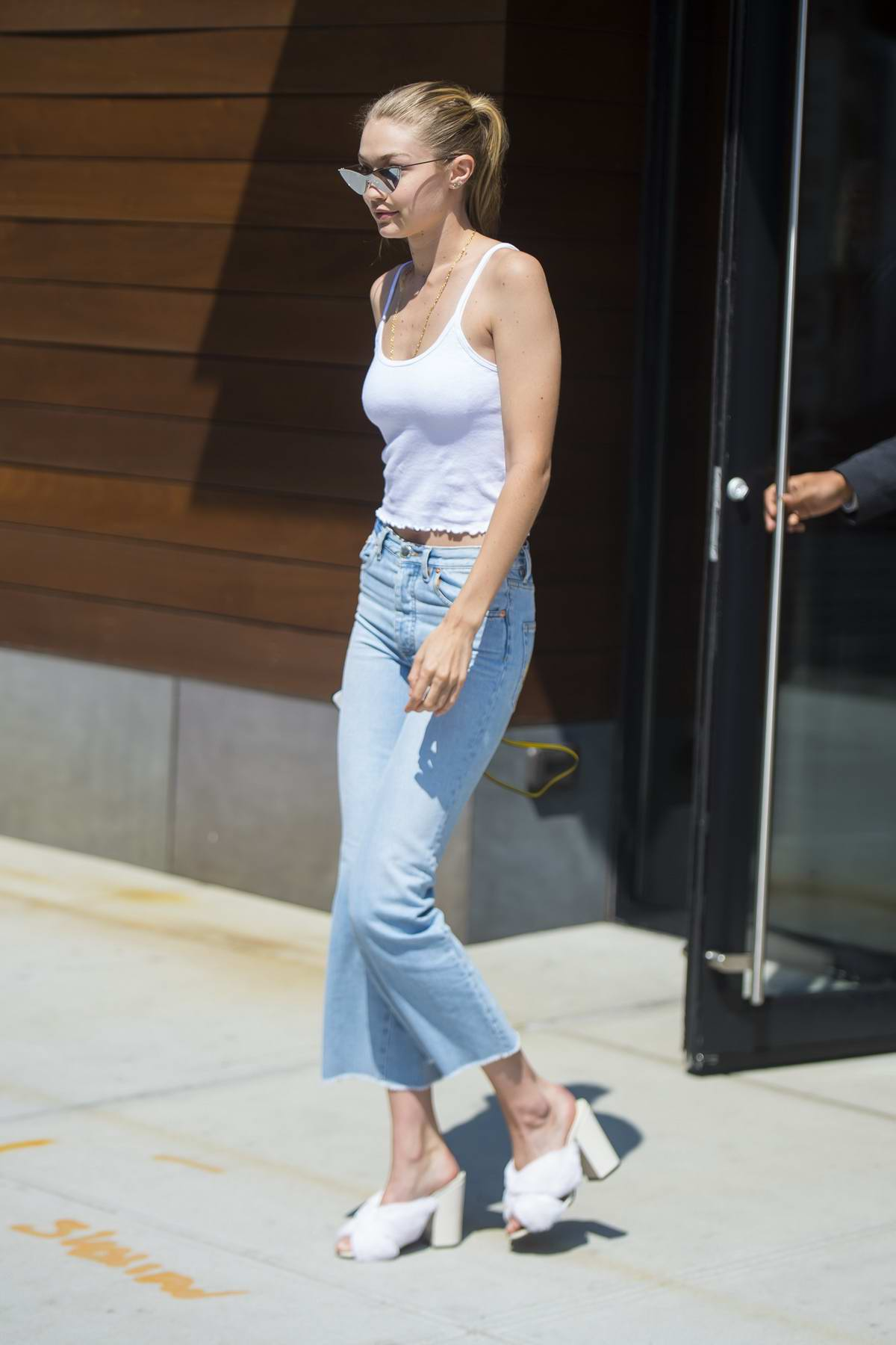 83836c5f gigi hadid spotted wearing a white tank top and jeans and furry slippers  while leaving her apartment in new york city-050917_5