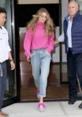 Gigi Hadid wearing a pink knit sweater and jeans as she leaves her apartment in New York City