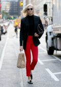 Karlie Kloss dressed in a black blaze and red pants while shopping in New York