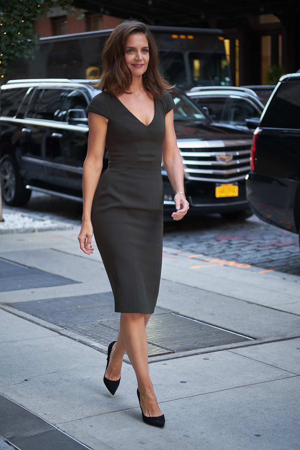 Katie Holmes wearing dark green while entering her hotel in New York City