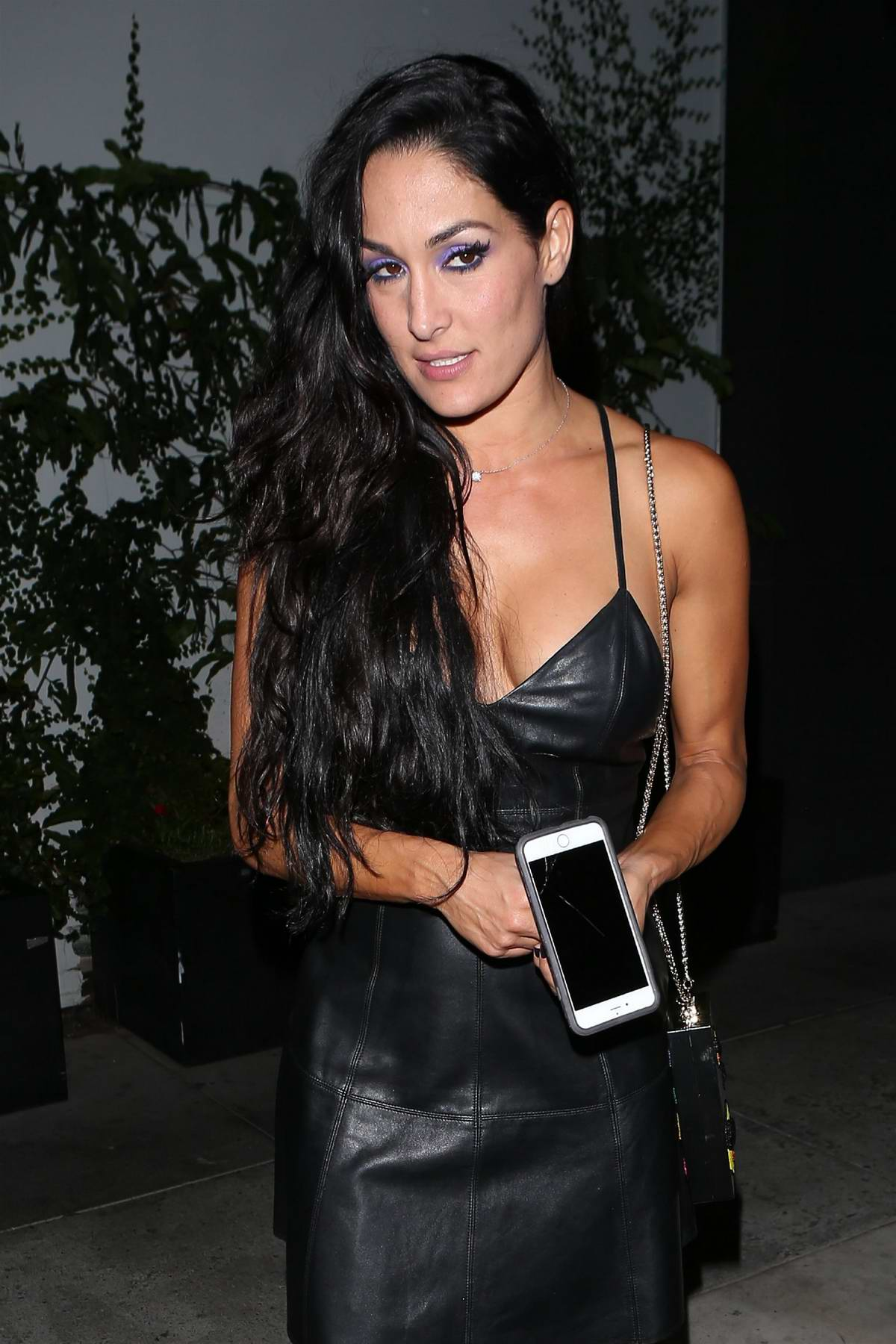 Nikki Bella in a black dress posing for fan photos leaving Beauty and Essex in Hollywood, Los Angeles