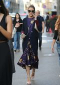 Olivia Palermo dressed in a blue cardigan over a purple dress looked busy on her phone while out in downtown Milan, Italy