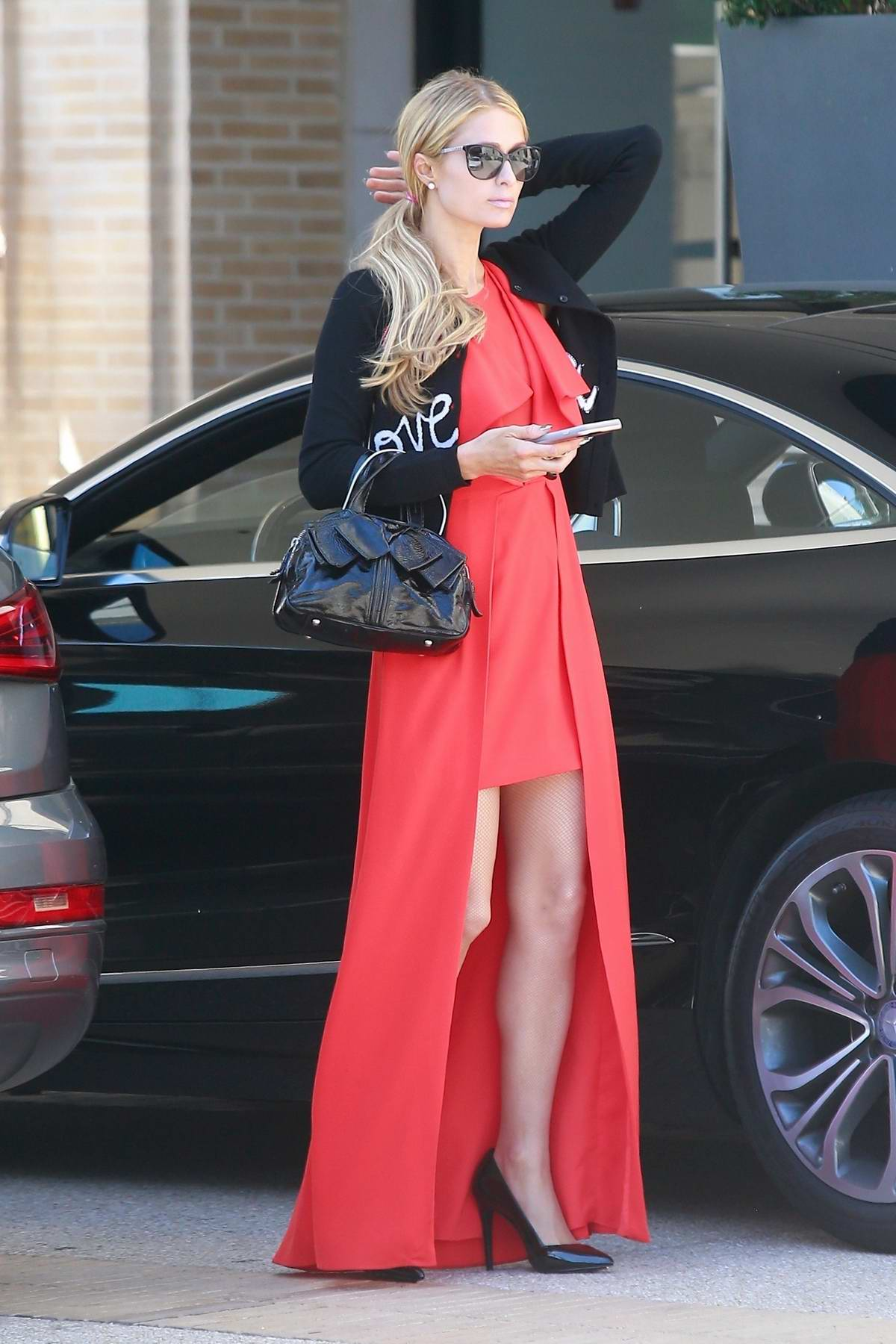 Paris Hilton stands out in a bright red dress as she goes shopping at Barneys New York
