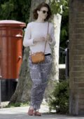 Rose Leslie listening to her iPhone while taking a walk in London