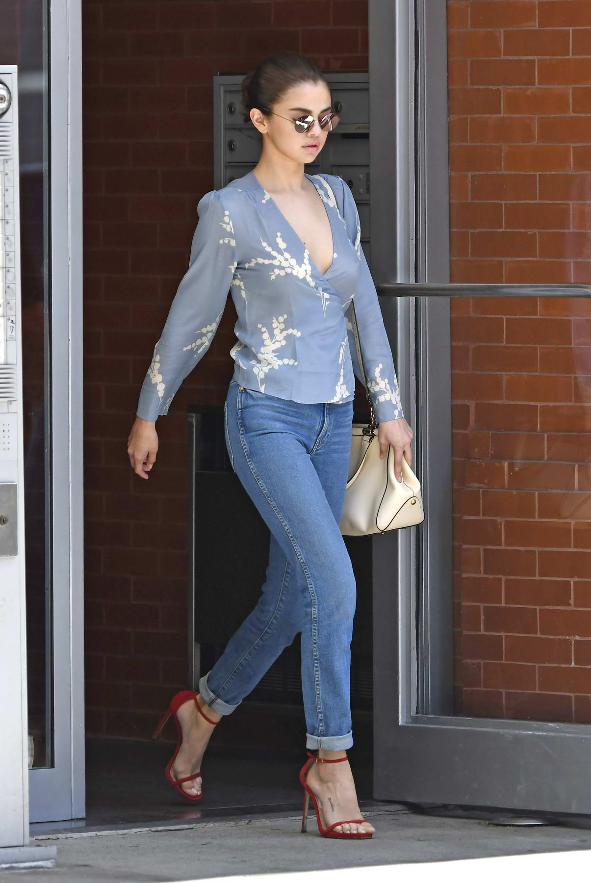 Selena Gomez wears denim and a blue floral top on her way to the Woody Allen film-set in New York City
