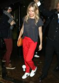 Sienna Miller in a grey tee and red pants leaves the Apollo Theatre in London