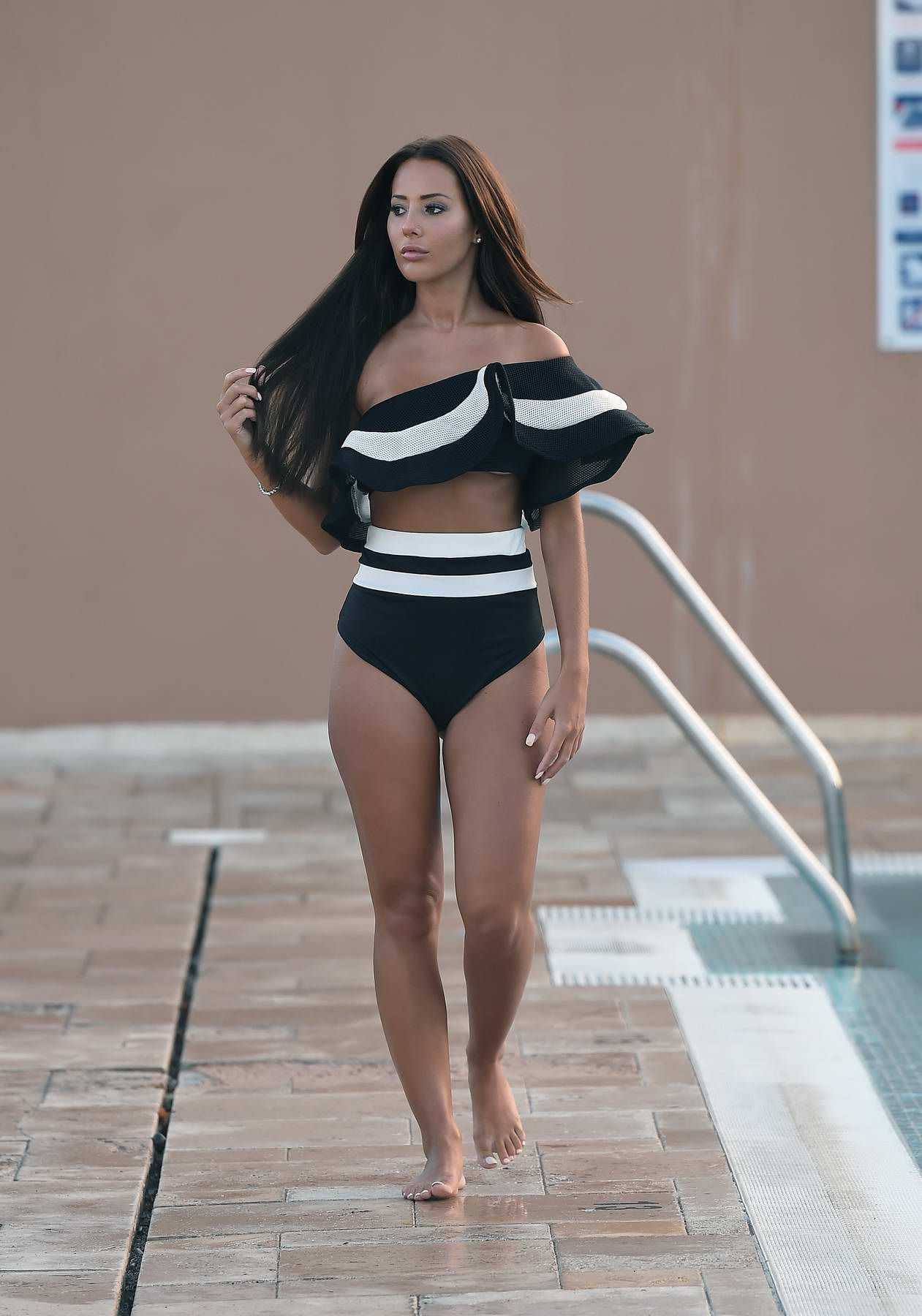 Yazmin Oukhellou in a black bikini spotted on a swimwear photoshoot in Marbella, Spain