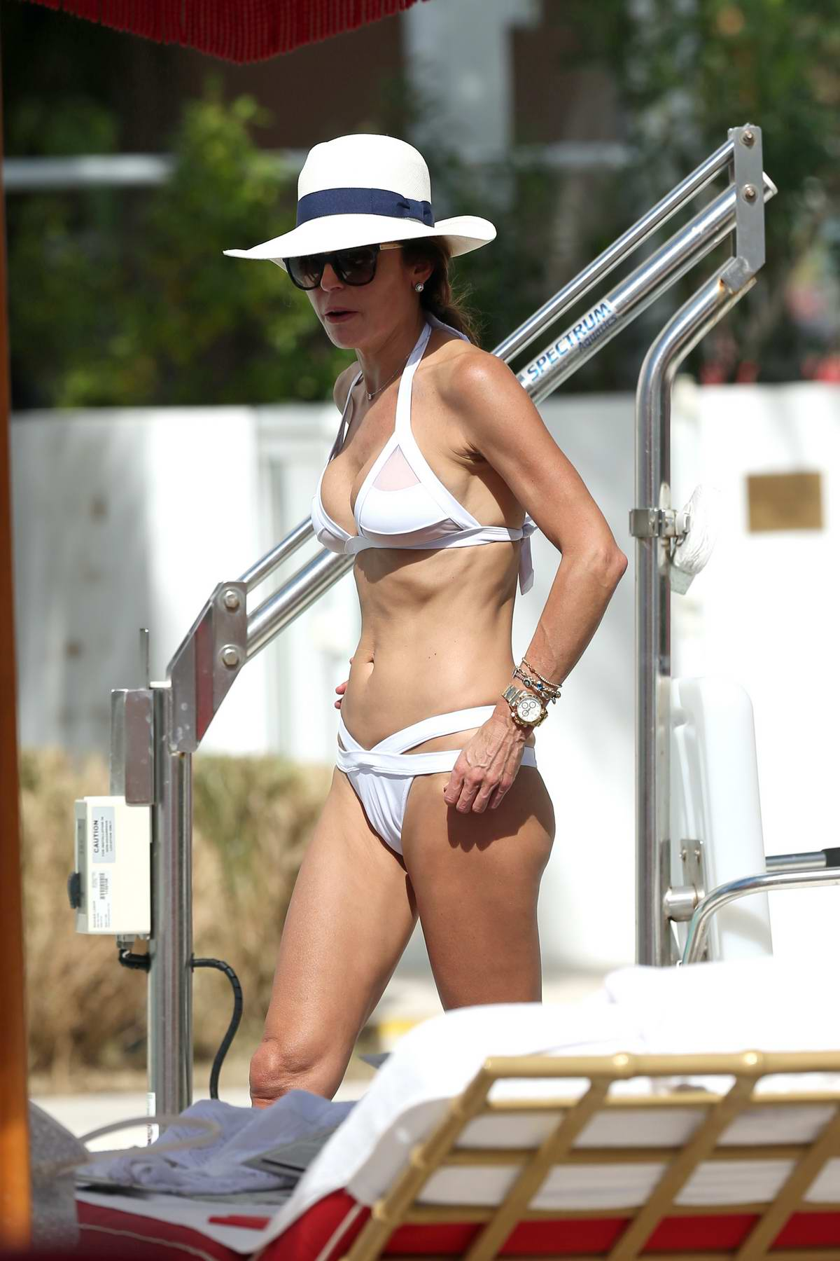 Bethenny Frankel in a white bikini relaxing by the pool in Miami, Florida