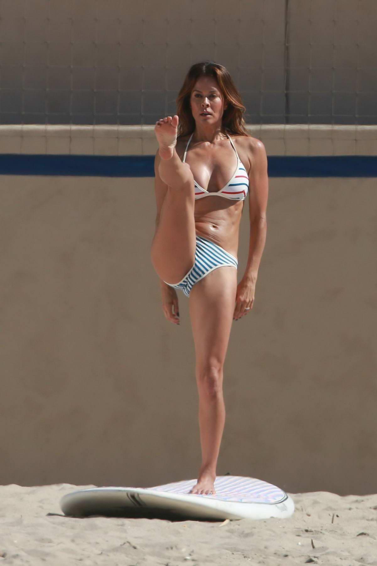 Brooke Burke in a striped bikini while filming a workout video on top of a surfboard in Malibu, California
