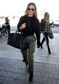 Chrissy Teigen in a black top with green pants is seen arriving at LAX Airport in Los Angeles