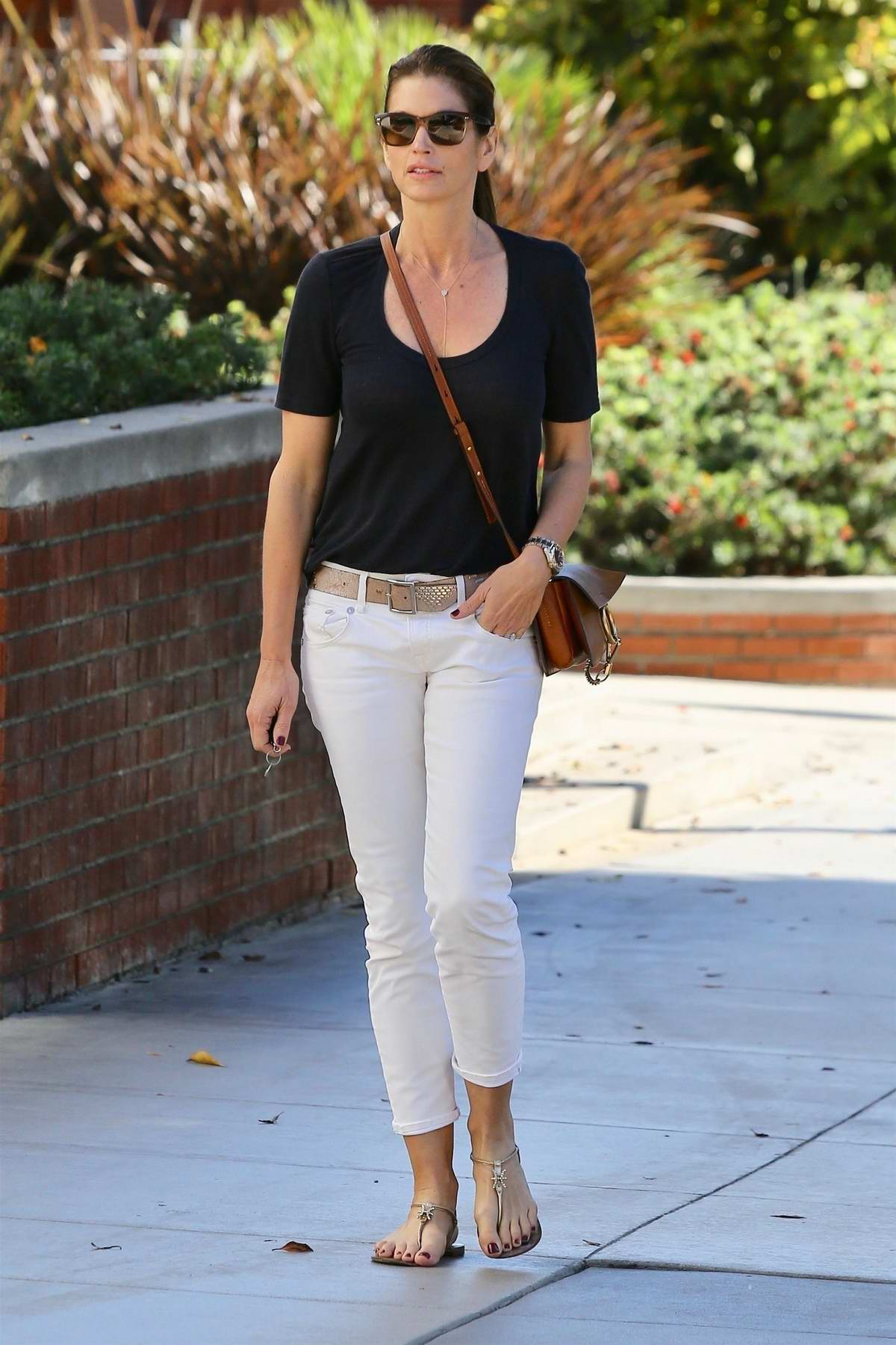 Cindy Crawford in a blue tee and white jeans seen running errands in Santa Monica, California