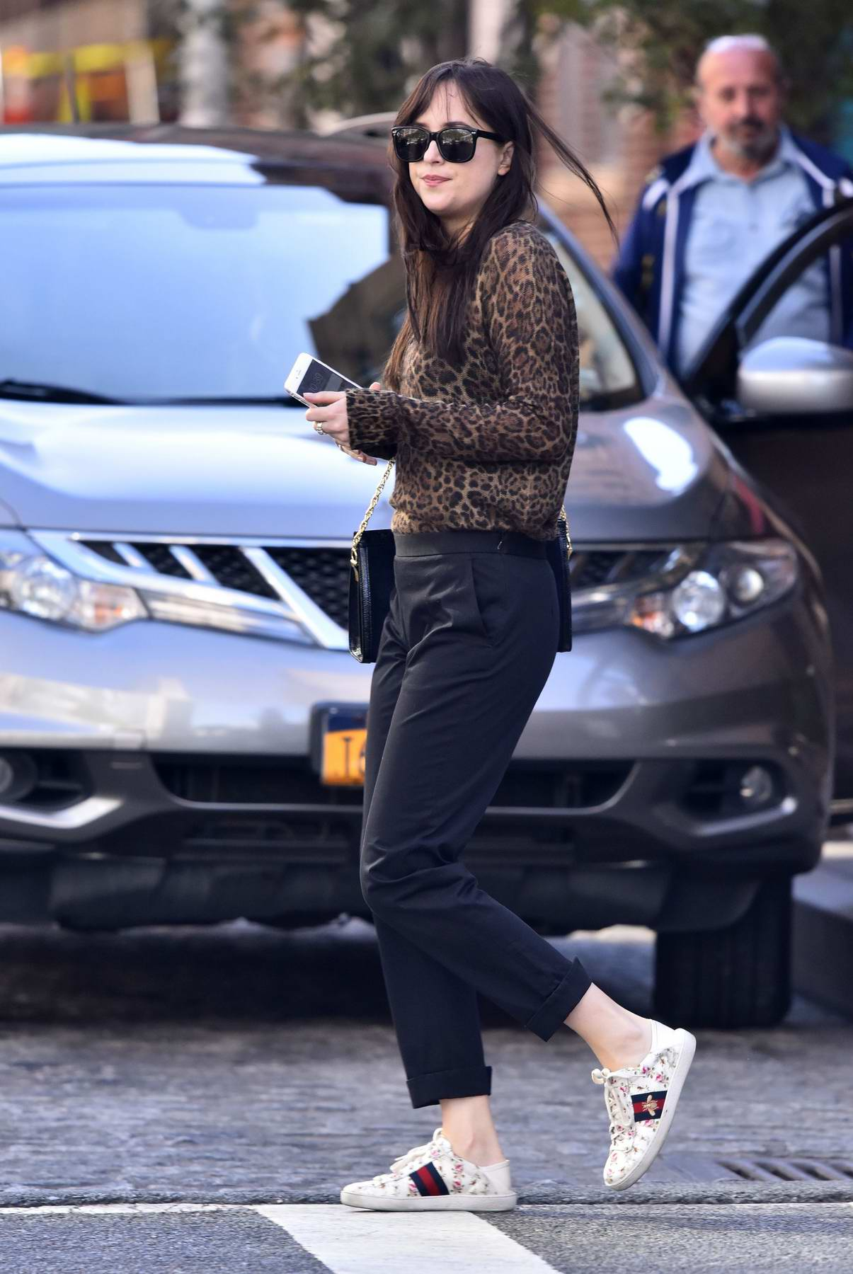 Dakota Johnson wears a leopard top paired with Gucci white sneakers while crossing the street in New York City