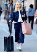 Elle Fanning pulls a rolling suitcase and carries a pink Miu Miu bag in the East Village, New York City