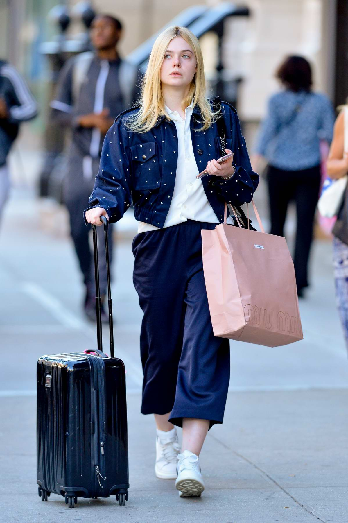7e9c75f393e49 Elle Fanning pulls a rolling suitcase and carries a pink Miu Miu bag in the  East Village