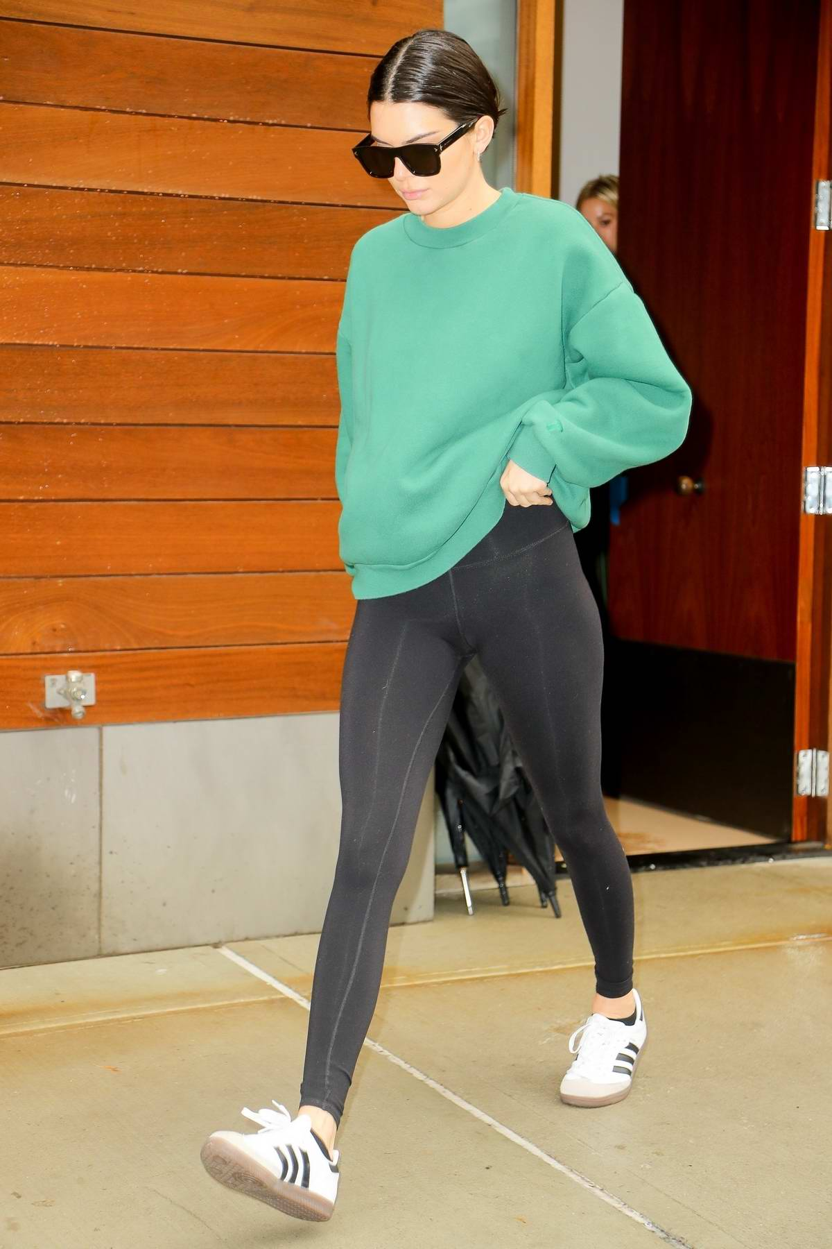 Kendall Jenner wears a green sweatshirt paired with black leggings while heading out in New York City