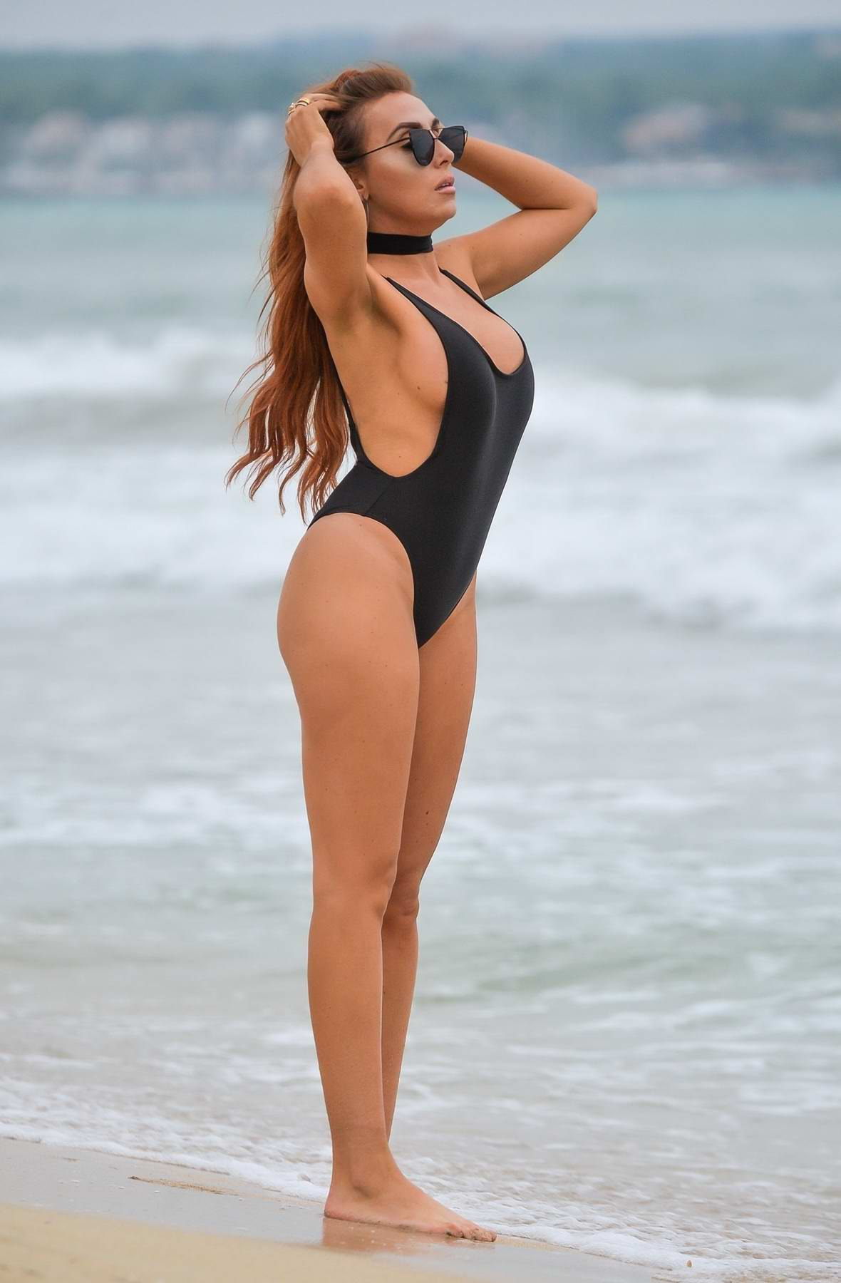 Laura Simpson in a black swimsuit enjoying the beach in Majorca, Spain