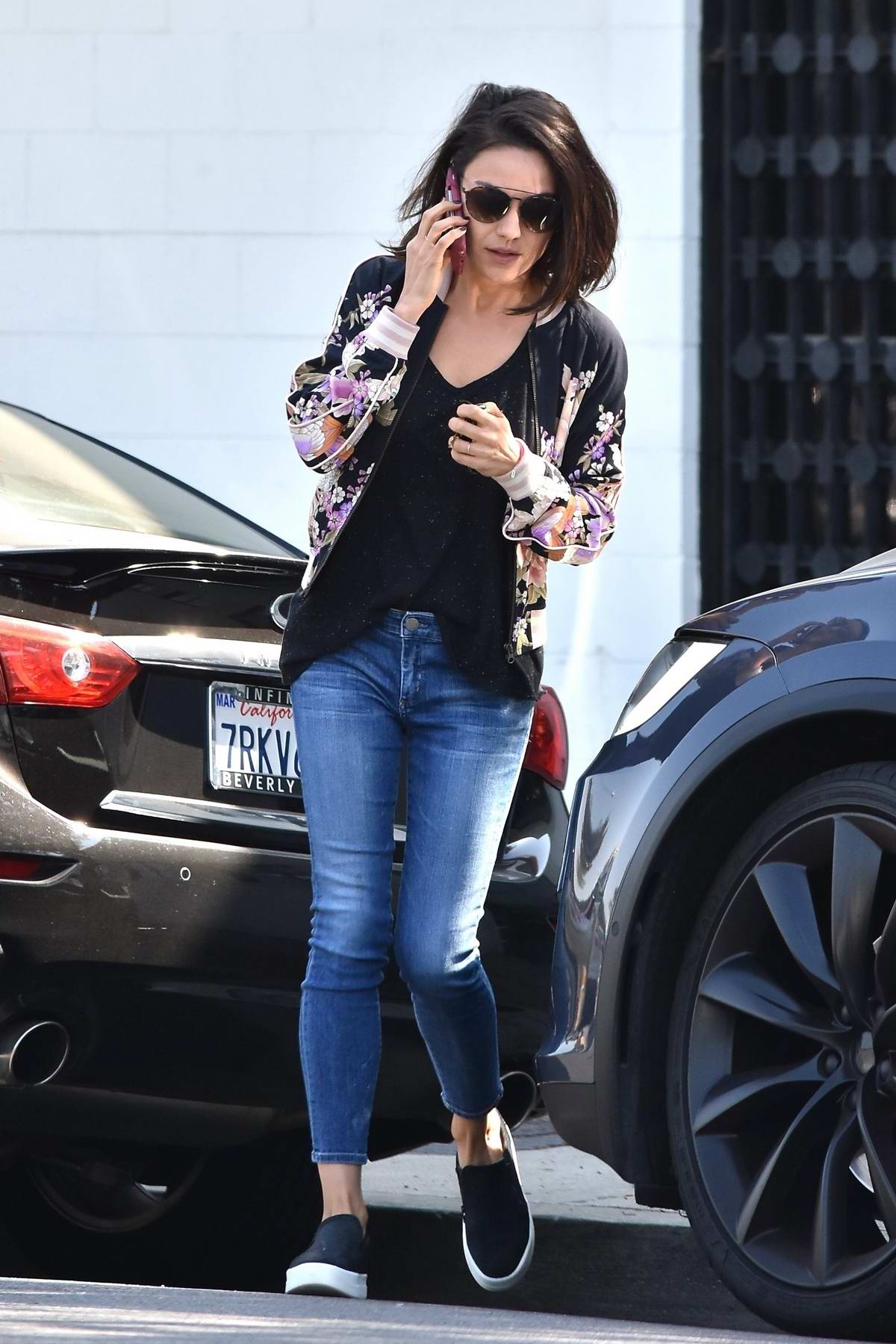 Mila Kunis busy on her phone while leaving a hair salon in Beverly Hills, Los Angeles