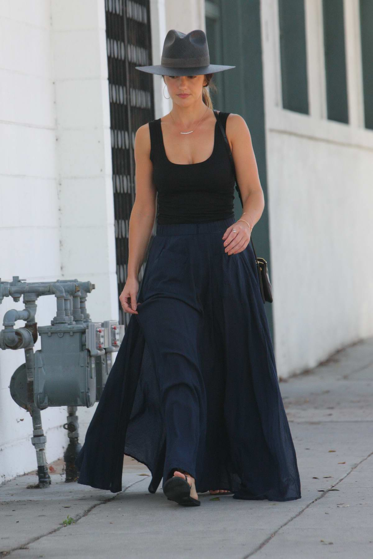 Minka Kelly wears a black tank top and long blue skirt with a hat while out in Beverly Hills, Los Angeles