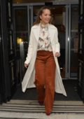 Rita Ora leaves BBC Radio Two in a white overcoat and rust coloured pants in London