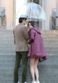 Selena Gomez in a burgundy jacket over a yellow top and red skirt filming rain scene with Timothee Chalamet for Woody Allen project in New York City
