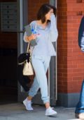 Selena Gomez steps out of her apartment holding a laptop in New York City