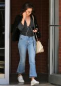 Selena Gomez wearing a black polka dotted shirt with blue jeans while leaving her apartment New York City
