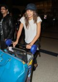 Taylor Hill pushes her luggage after touching down at LAX Airport, Los Angeles